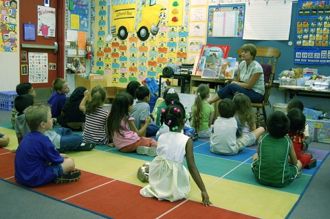 A teacher reads a story to kindergarteners (click for credit)